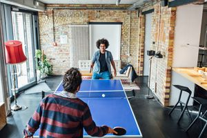 Two business colleagues playing table tennis at creative office