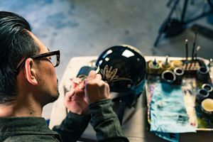 An artist customizing a motorcycle helmet.