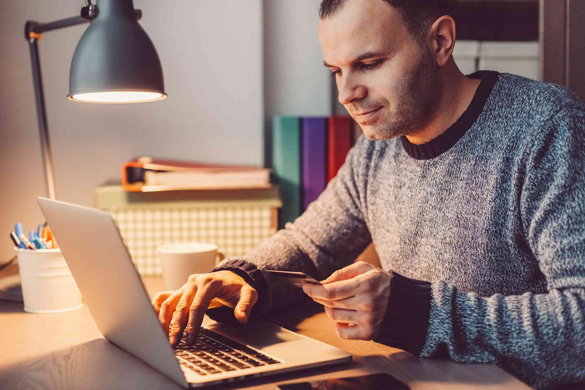Man at home shopping online with credit card