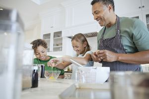 A happy father cooking with his children.