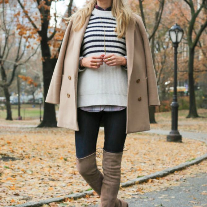 Woman in striped sweater and camel coat with tall boots