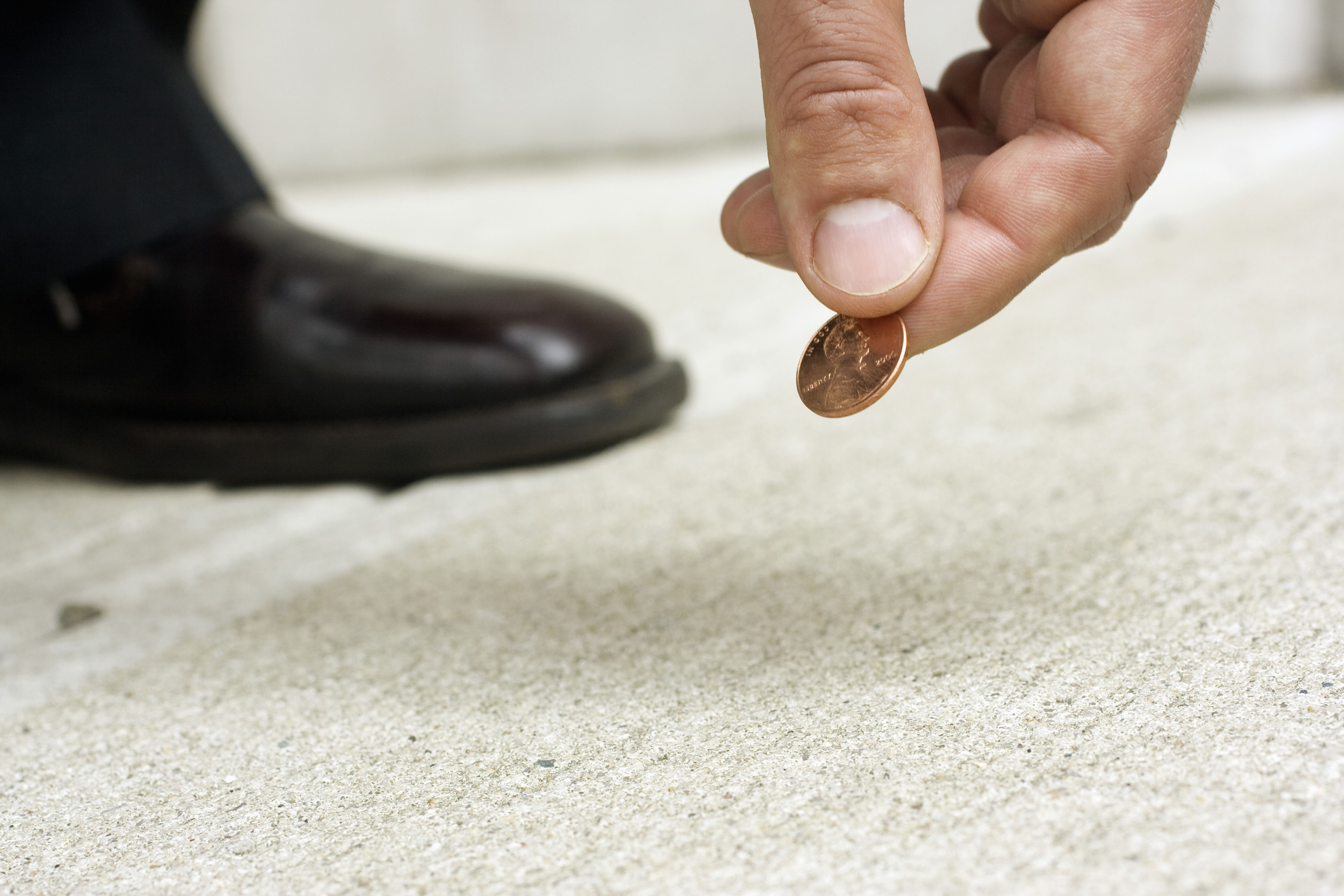 Close up of man picking up penny from street