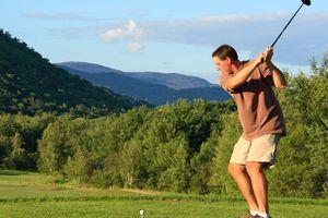 Golfer preparing to hit tee shot, hoping not to whiff