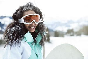 Young woman wearing ski goggles outdoors on snowy day