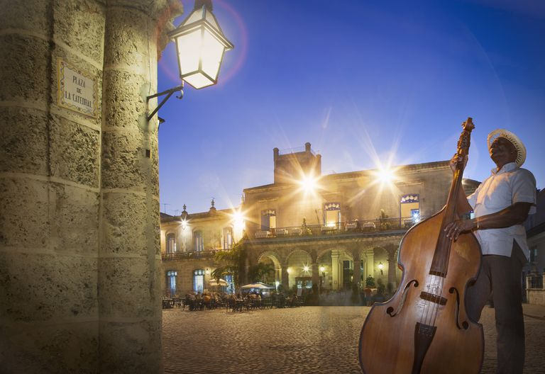 Senior man playing double bass in Plaza de la Cathedral at night, Havana, Cuba