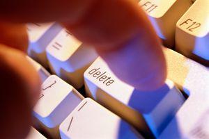 Finger pressing 'delete' key on computer keyboard, close-up