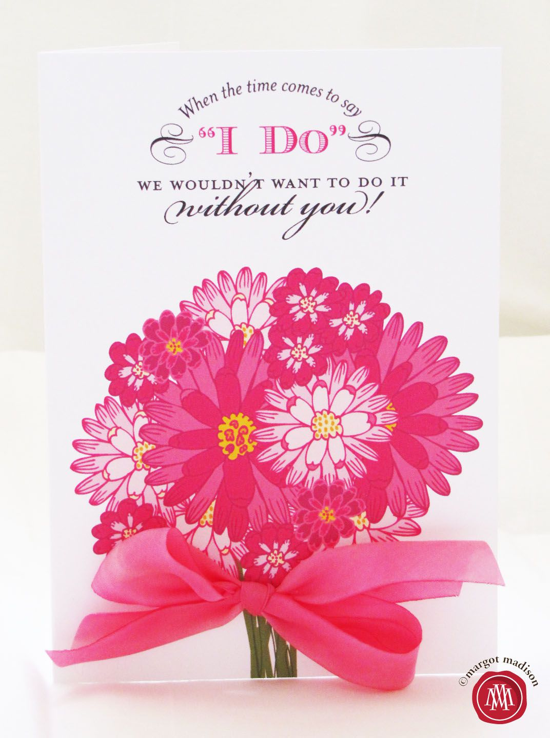 A pink bouquet on a Will You Be My Bridesmaid? card.