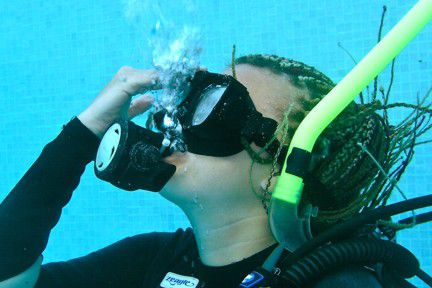 A scuba diver exhales to clear her scuba mask of water.