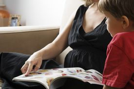Pregnant mother and son (3-5) reading catalogue, close-up