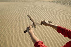 Woman holding dowsing rod in desert