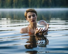 woman holding crystal ball in lake.