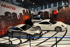 Real-life cars in front of Need for Speed Most Wanted wall poster
