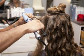Young woman getting her hair done in salon