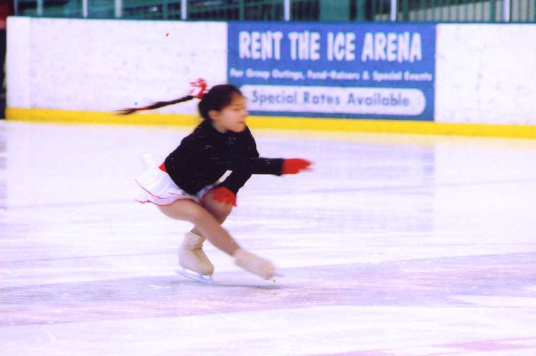 A Young Figure Skater Does a Sit Spin On the Ice