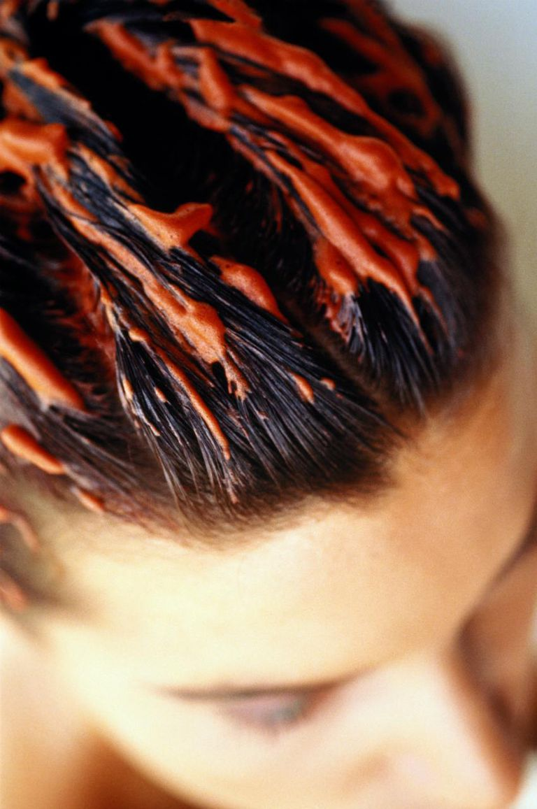 Woman with orange colouring mousse combed through wet hair