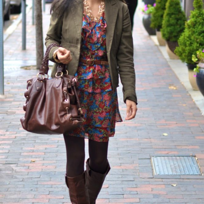 Woman wearing a printed dress and blazer with tall boots