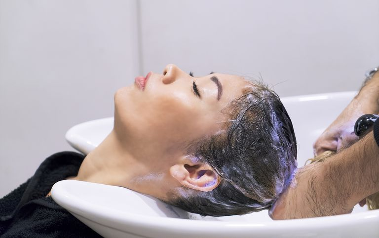 Asian woman at a salon getting blonde highlights toned