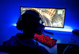 Person wearing headphones and playing a PC game