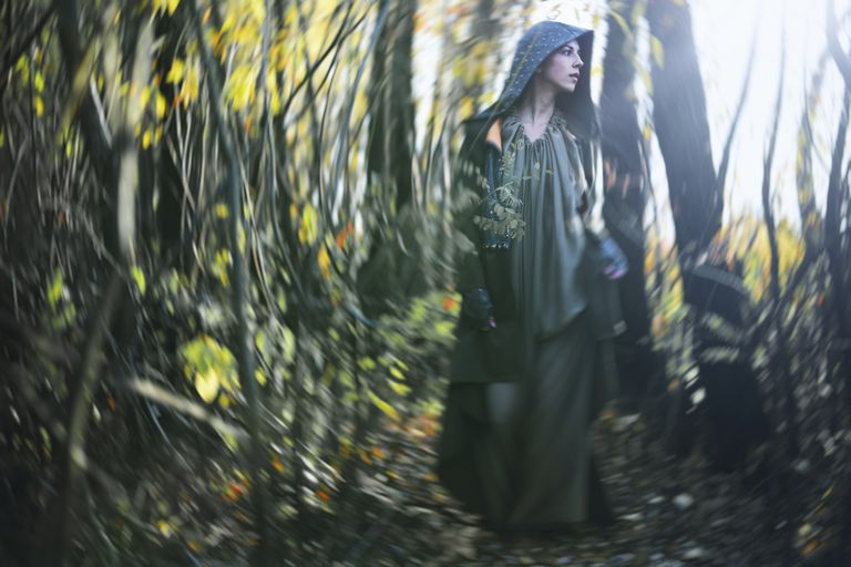 A cloaked woman walks through a forest