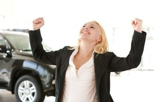 Happy and excited businesswoman in car showroom with hands raise
