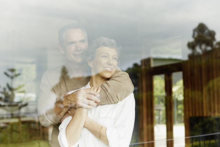 Thoughtful couple looking through window