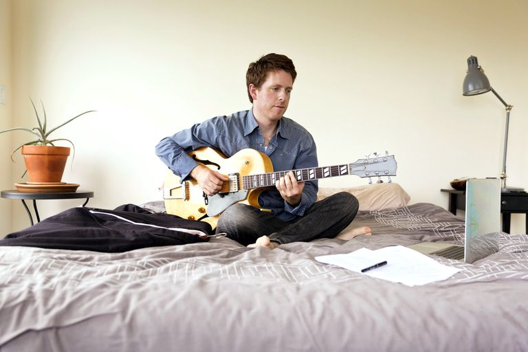A guitarist practicing songs on his bed, reading off a laptop