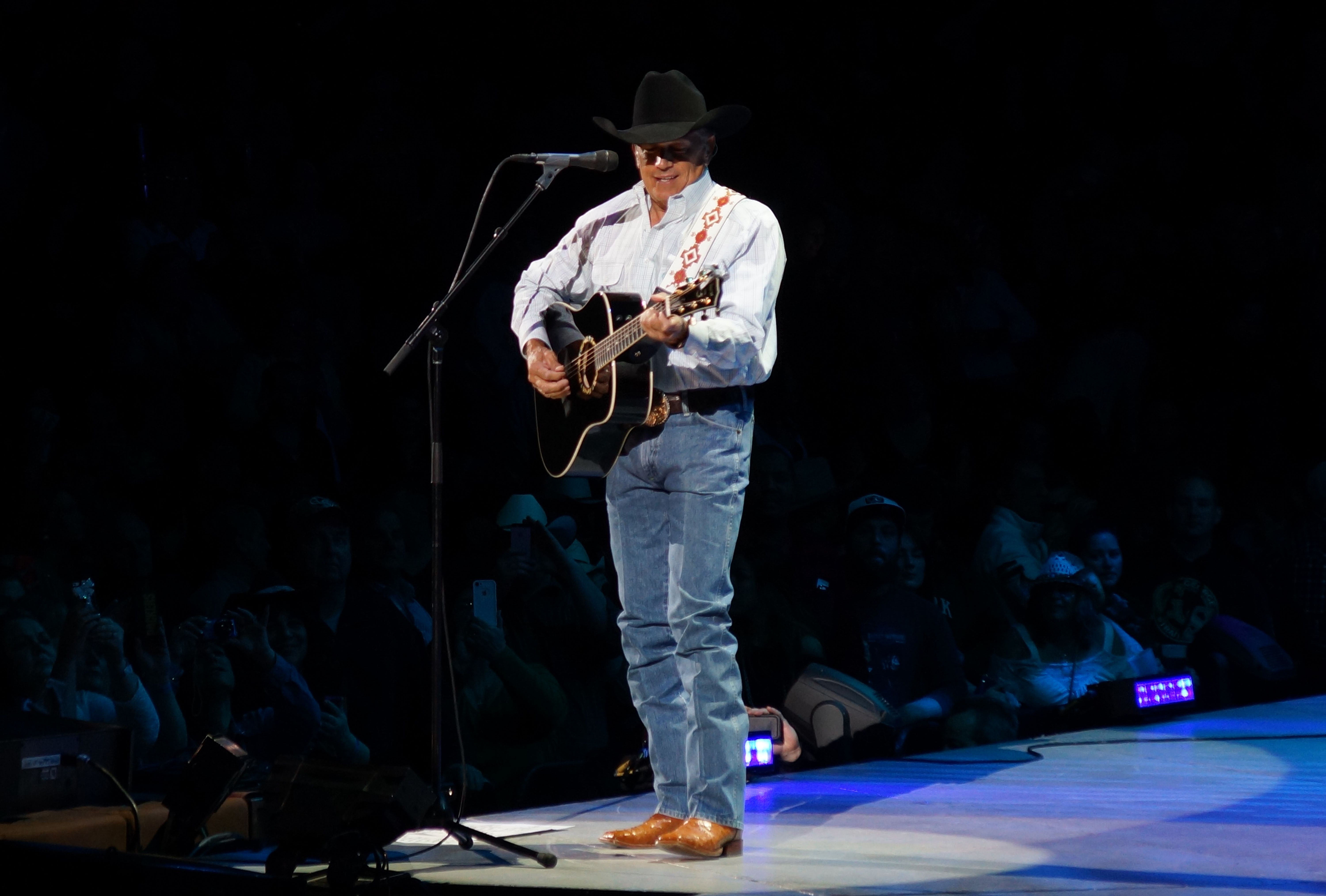 George Strait standing in a spotlight performing on stage.