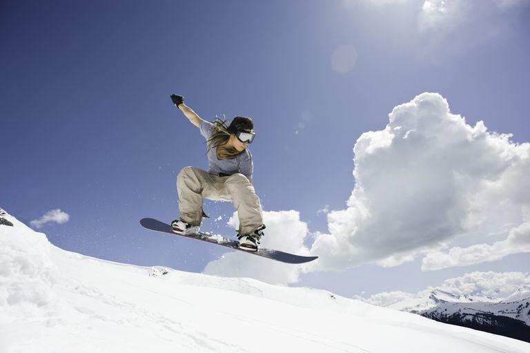 Female snowboarder jumping through air