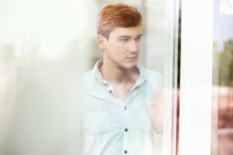 Unhappy young man looking out of window