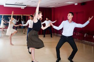 Adult people dancing lindy hop in pairs