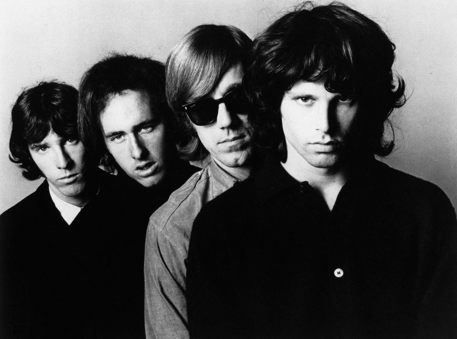 Black and white promotional photograph of The Doors with singer Jim Morrison in front.