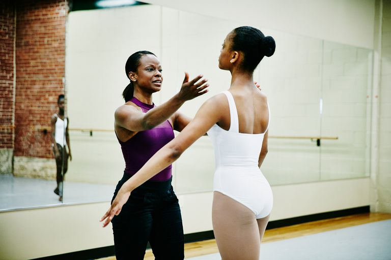 Ballet instructor adjusting dancers form.