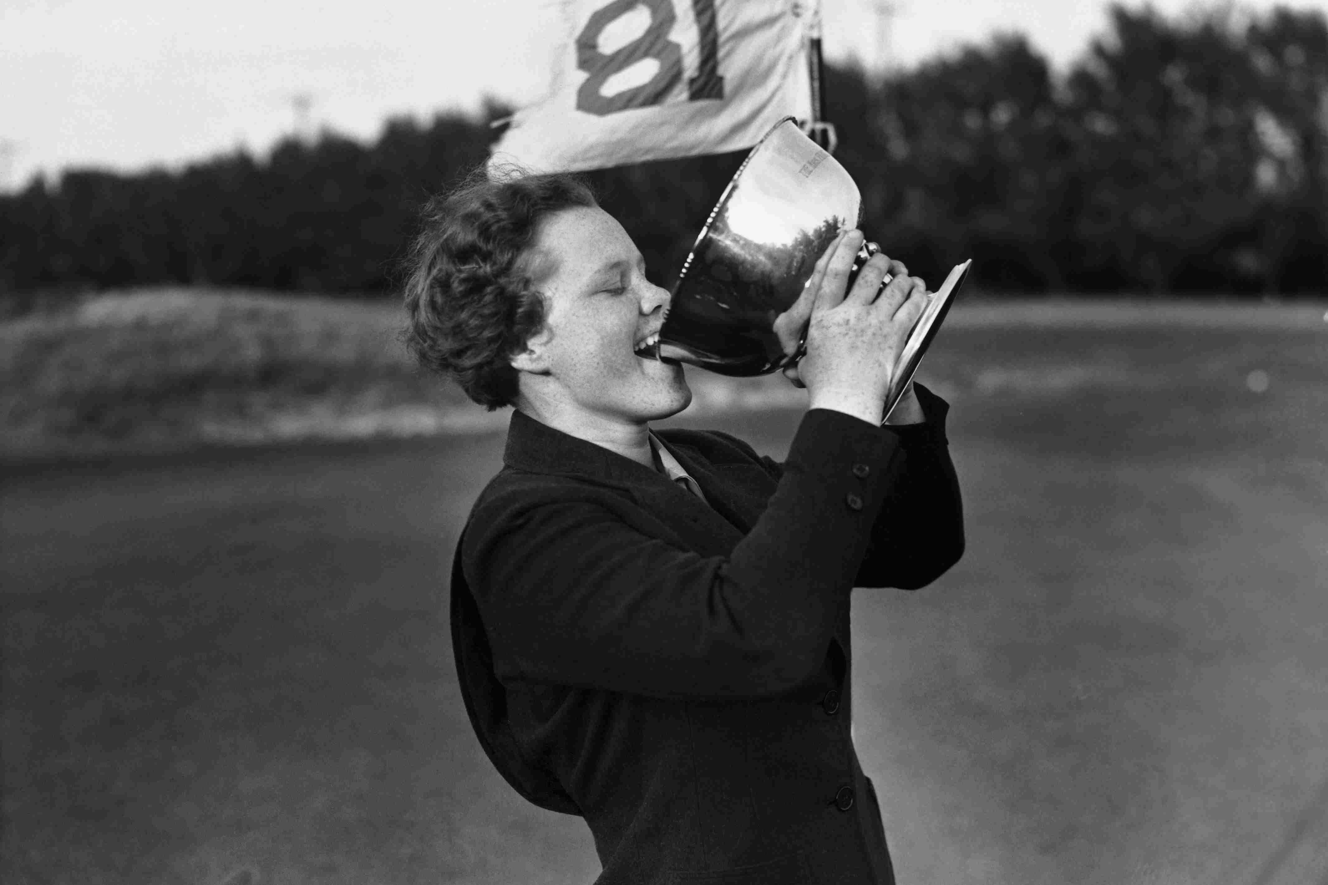 Patty Berg drinking from a golf trophy