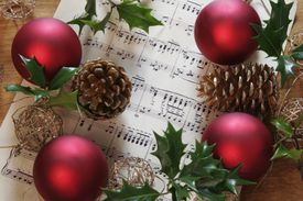 Christmas scene with holly, fir cones and, sheet music