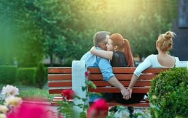 Woman embracing man on bench while man holds hands with another woman