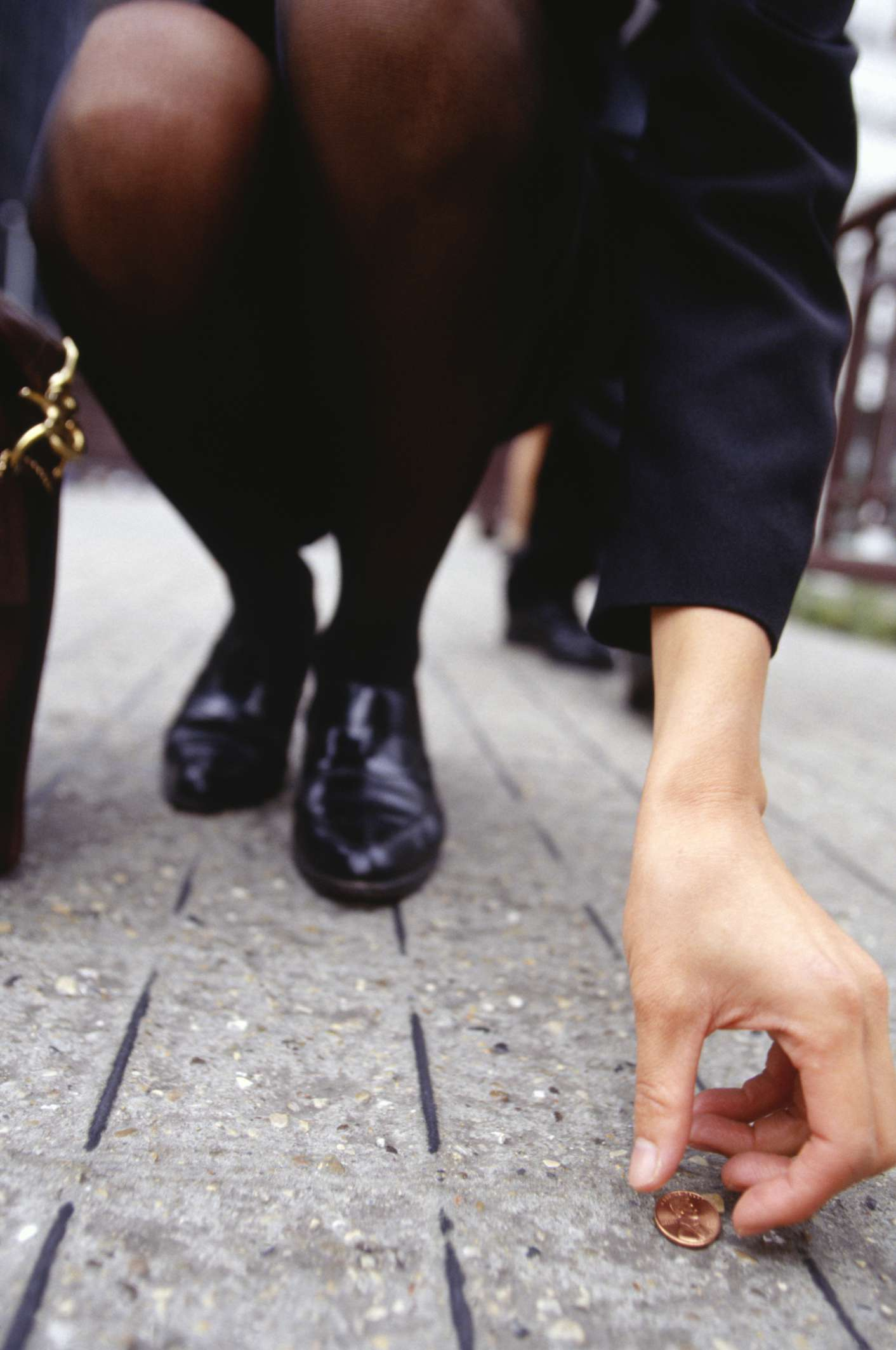Image of a businesswoman picking up a lucky penny.