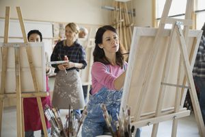 woman painting on canvas in art studio
