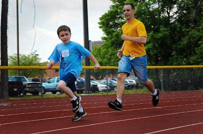 Logistic Specialist 2nd Class William Hoffman runs with a Special Olympics participant at the 14th annual Georgia Area 16 Special Olympics at Naval Submarine Base Kings Bay