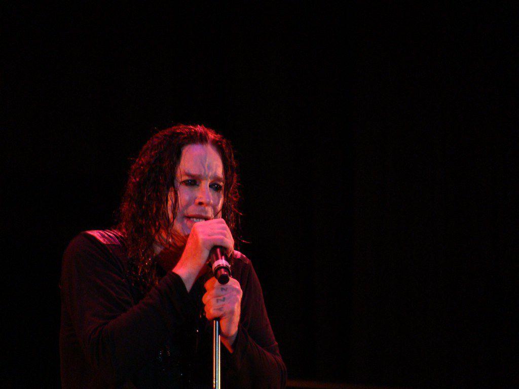 Ozzy Osbourne singing on a dark stage.