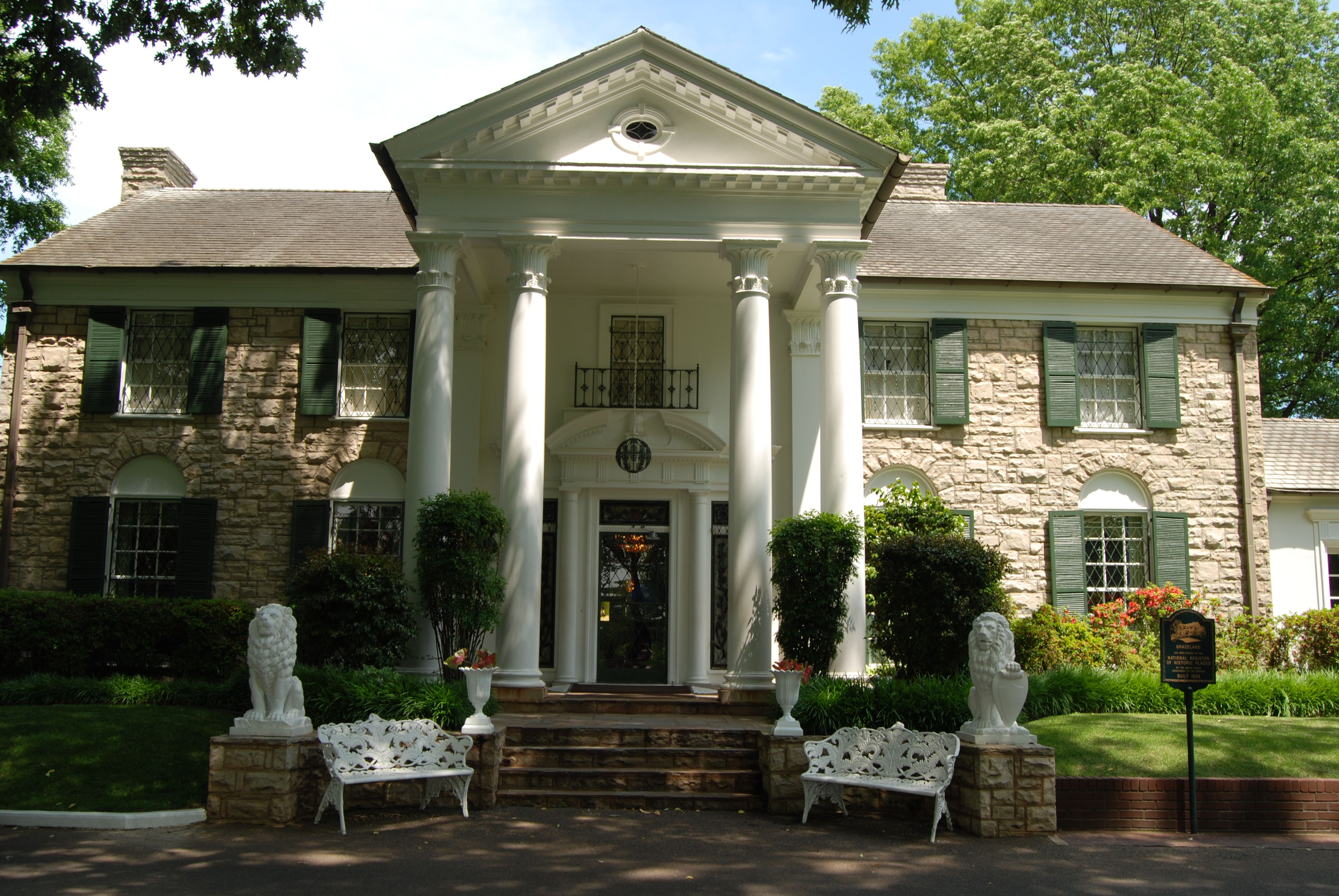two-story stone mansion with rusticated limestone facade, neoclassical in style with front columns, portico, and pediment