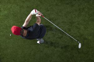 A golfer swinging a golf club, overhead view