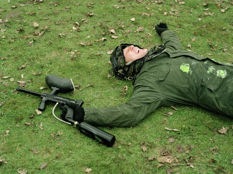 Paintballer lying on grass