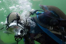 Diver underwater in profile.