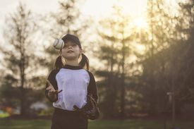 Girl throwing baseball up into the air