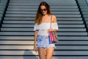 Woman in summer outfit of denim shorts and off the shoulder blouse