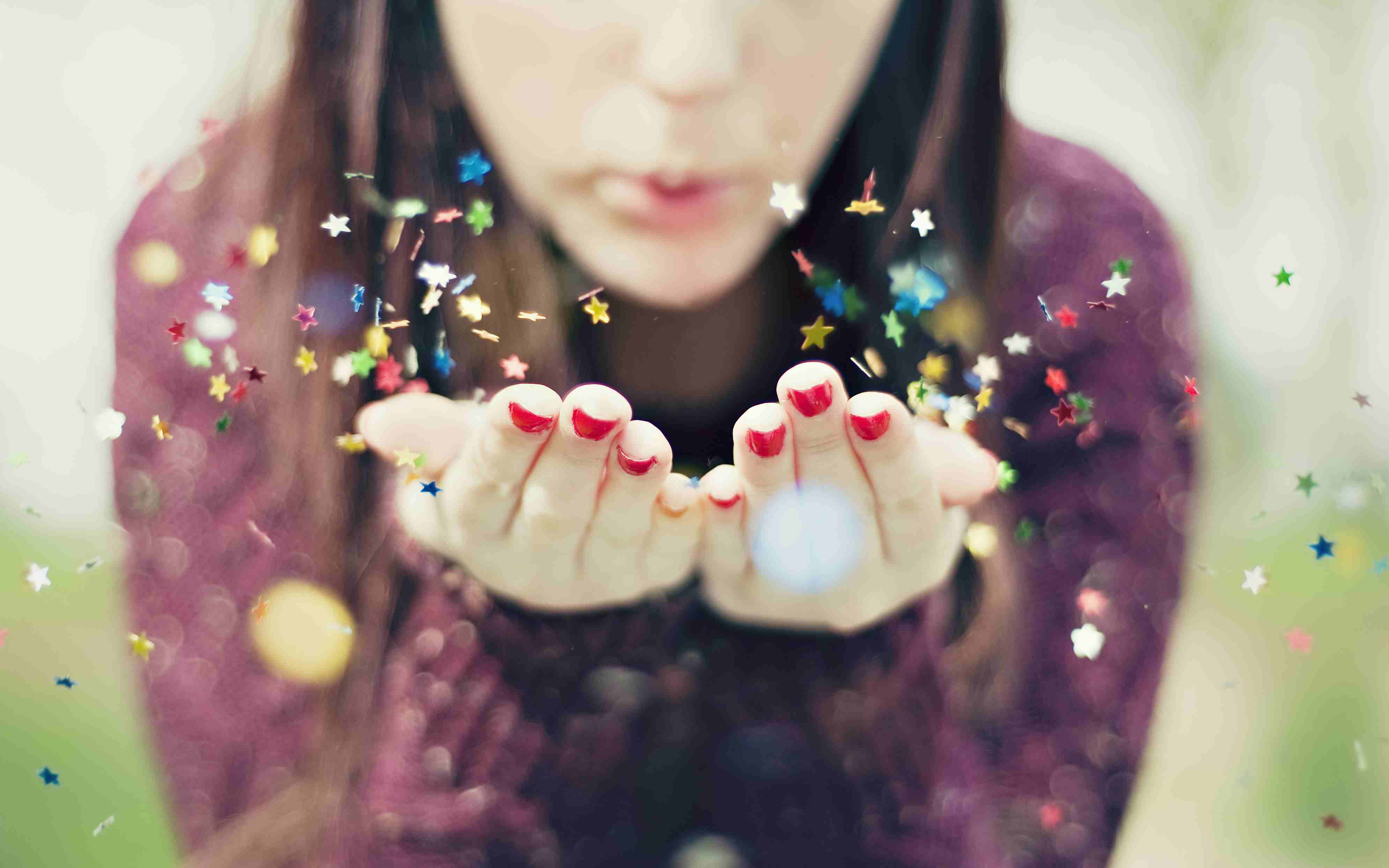 Young woman blowing star confetti