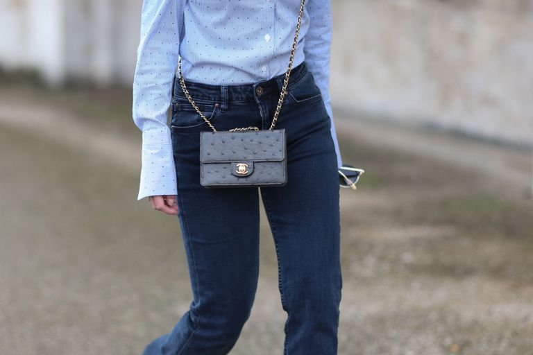 Woman wearing dark blue jeans and Chanel purse