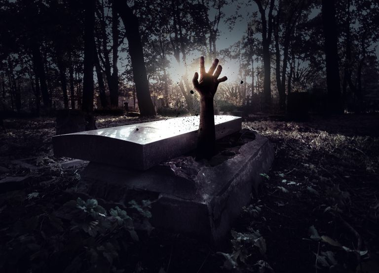 Hand coming out of a coffin in the ground