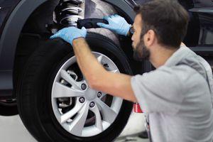 auto repair technician inspecting shock absorber