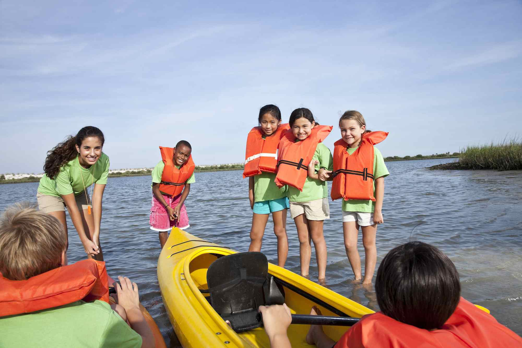 Summer camp counselor and children with kayaks